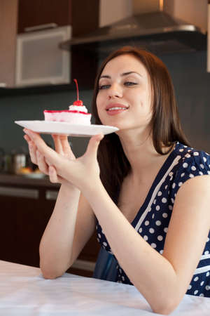 admires: Young woman admires her cake Stock Photo
