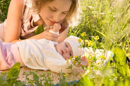 bebes recien nacidos: Hermoso bebé y su madre están mintiendo en la hierba