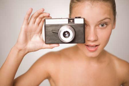 jeune fille adolescente nue: Nu jeune fille tient un vieil appareil photo démodé, sur fond blanc