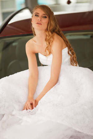 bonnet: Young sensual bride sits on the  red car bonnet