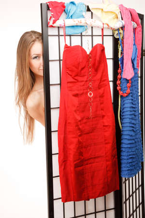 screen partition: Young woman is Looking out of the folding screen,a lot of different clothes is is hanging on it Stock Photo