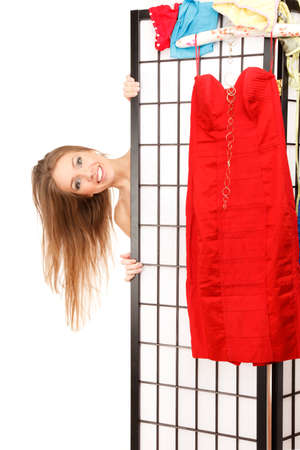 screen partition: Young beautiful woman looks out of the folding screen , red dress is hanging on it Stock Photo