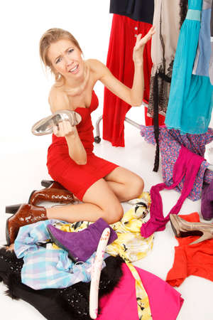 clothes rack: Young woman sits near her clothes rack with lots of dresses,and some clothes is on the floor,and she is holding her shoe and scream!