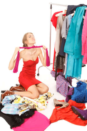 choking: Young woman sits near her clothes rack with lots of dresses,and some clothes is on the floor,and she is choking her self with her pantyhose