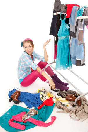 clothes rack: Young woman sits near her clothes rack with lots of dresses,and some clothes is on the floor