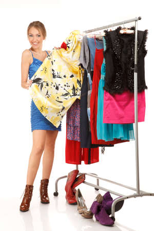 clothes rack: Woman is choosing dresses . She stands near her clothes rack with lots of dresses