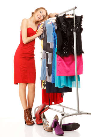 clothes rack: Young woman stands near her clothes rack with lots of dresses,and embraces clothes. Stock Photo