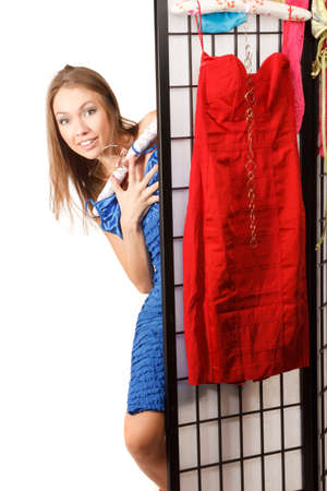 screen partition: Young beautiful woman looks out of the folding screen ,with red dress hang on it