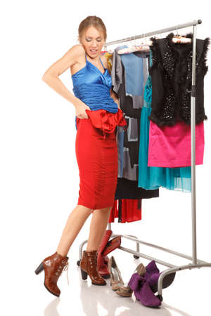 trying on: Woman is trying on dresses ;near her clothes rack with lots of dresses Stock Photo
