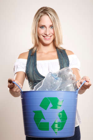 recycling bin: Woman holding a recycling bin filled with plastic.Studio shoot