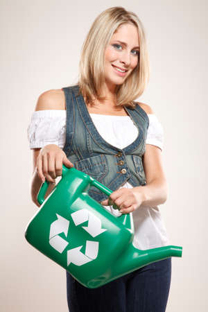 going green: Going green! Woman holding a green watering pot with recycling sign Stock Photo