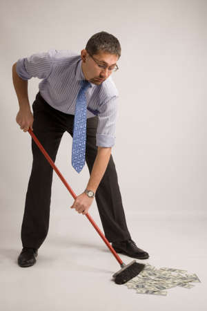 rolledup sleeves: Businessman with rolled up shirtsleeves is sweeping dollars