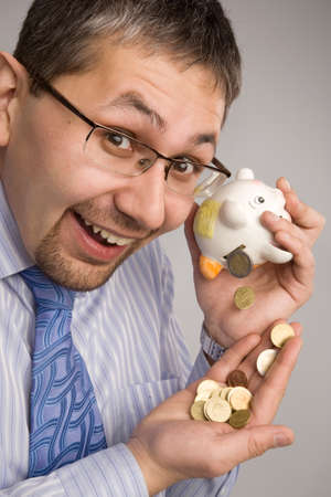 account executive: Coins form piggy bank are falling to the business mans hand Stock Photo