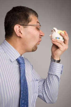 account executive: Businessman is holding a piggy bank in front of his face and making a funny grimace