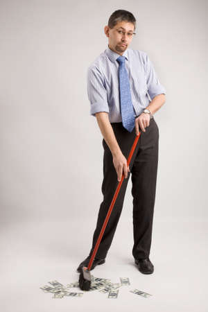 rolledup sleeves: Businessman with rolled up shirtsleeves is sweeping dollars, isolated on  white background Stock Photo