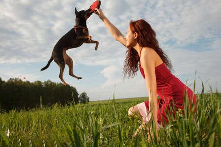 persona saltando: Hermosa mujer joven que juega con su perro en el parque.