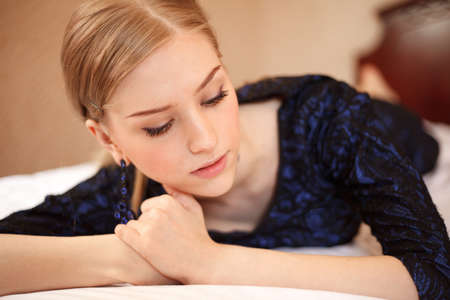 Young girl in blue dress is lying on the bed