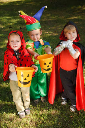 Three boys in halloween costumes are counting their candies