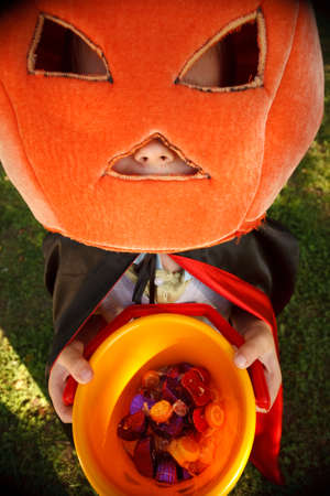 wideangle: Boy in big pumpkin hat trick or treating.Shooted with wide-angle lens effect Stock Photo