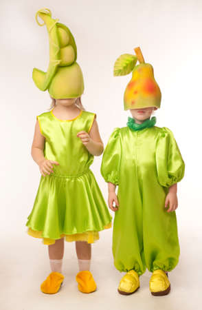 pea pod: Sweet little boy and girl in costumes of fruit - pear and pea pod with their hats on eyes
