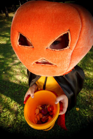 Boy in pumpkin hat trick or treating.Shooted with wide-angle lens effect Stock Photo