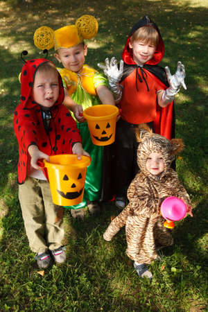 trick or treating: Four boys in halloween costumes trick or treating