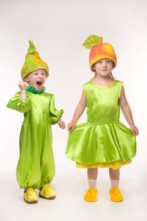 pea pod: Sweet little brother and sister are playing with their costumes - pear and pea pod Stock Photo