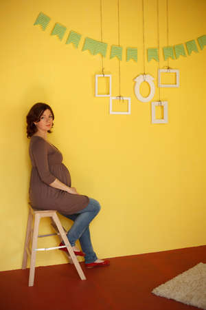showcase interiors: Pregnant woman sits near yellow wall with empty frames hanging on it Stock Photo