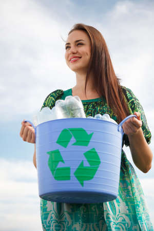 recycling bin: Young woman holding a blue recycling bin with plastic bottles