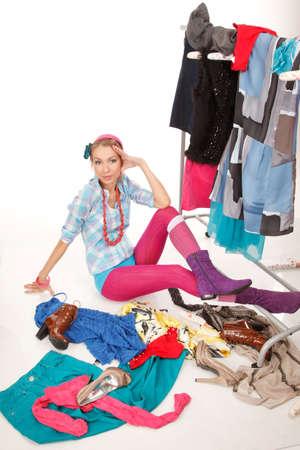 La mujer joven se sienta cerca de su ropa de rack con un montón de vestidos, y algo de ropa está en el piso