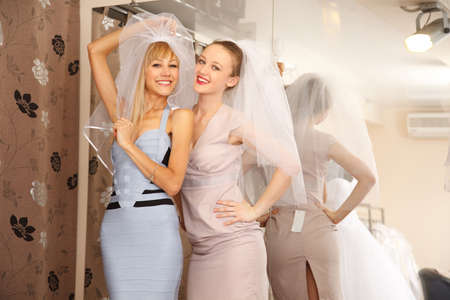 veils: Two girlfriends, A Bride-To-Be and bridesmaid having fun by Trying On A Wedding veils