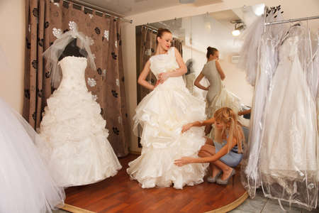 A Bride-To-Be shopping  with her girlfriend for a wedding dress in a Bridal Boutique.