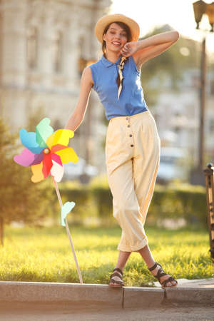 artificial model: Young happy funny (vintage) dressed woman on the street with colorful weather vane,looking like flower Stock Photo