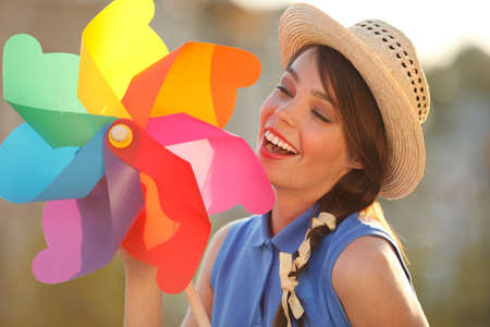 artificial model: Young happy funny (vintage) dressed woman with colorful weather vane,looking like flower