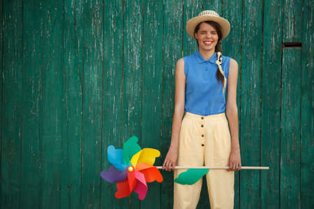 Young happy funny (vintage) dressed woman with colorful weather vane,looking like flower. Old green fence on the background. Stock Photo