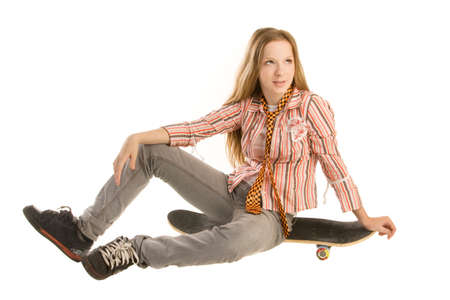 adolescencia: Teenage girl is sitting on skateboard, looking up,isolated on white background.