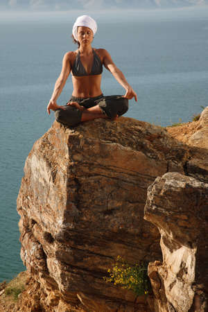 Real yoga instructor practicing on the rock near water line Imagens