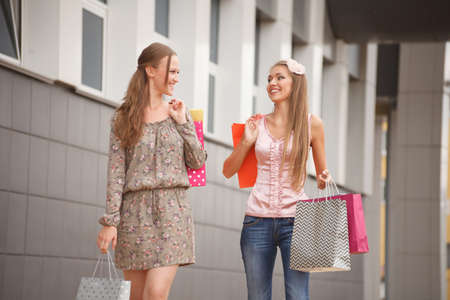 Two young cheerful women with shopping bags outdoors Stock Photo