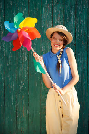 illustrating: Young happy funny (vintage) dressed woman with colorful weather vane,looking like flower Picture ideal for illustrating woman magazines.
