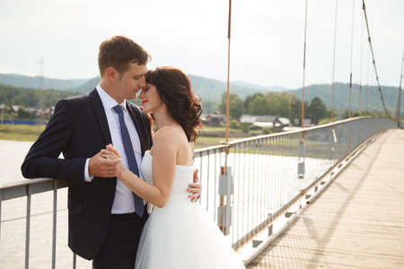 rive: Happy young bride and groom stand on the suspension bridge Stock Photo