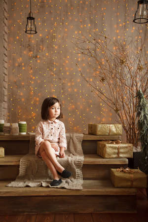 Stylish little girl in light pink dress sits in the christmas decorations