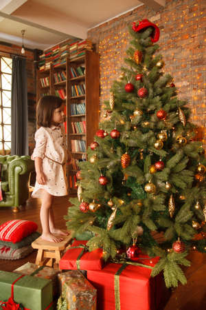 Little girl  is decorating christmas tree, with the presents underneath it