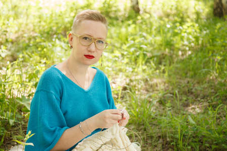 Hipster looking woman  in glasses knitting outdoors