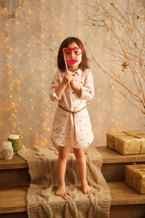 Stylish little girl in the christmas decorations with masks on the sticks   shaped like glasses and lips