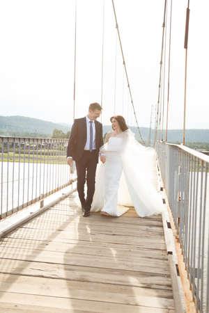 Happy young bride and groom are running across the suspension bridge