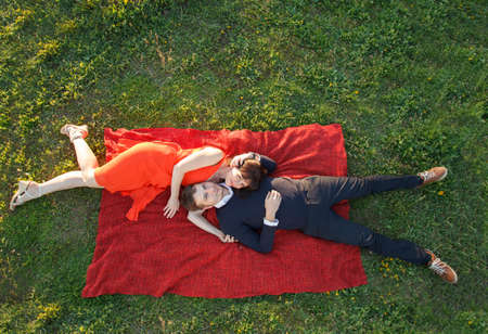 Young couple outdoors lying on the grass. High angle view