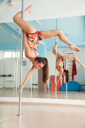 Young pretty woman  pole dancing in a dance hall