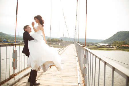 Happy young groom is carrying his wife across on the suspension bridge