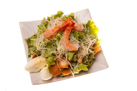 Salad with shrimps and eggs isolated on white