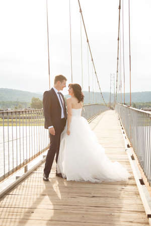 Happy young bride and groom stand on the suspension bridge Stock Photo